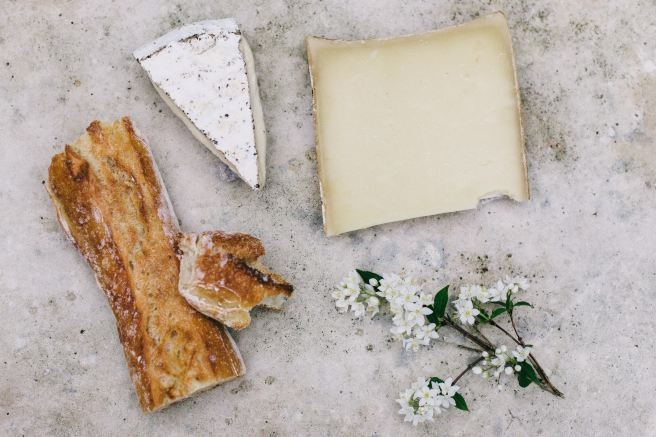 Cheese slices next to artisan crackers and white flowers