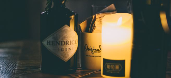 A bottle of Hendricks Gin with a candle