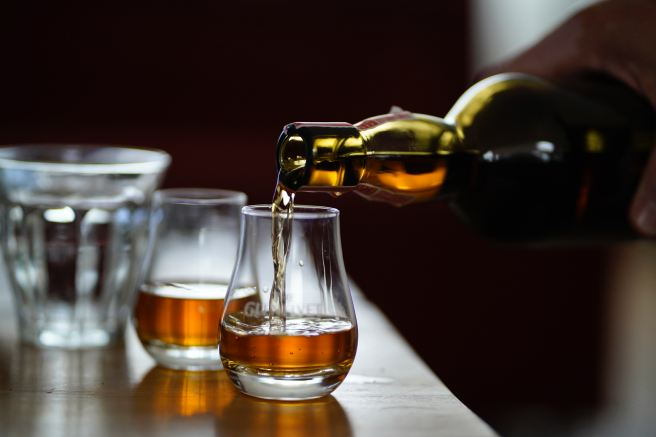 Person pouring whisky into two glasses