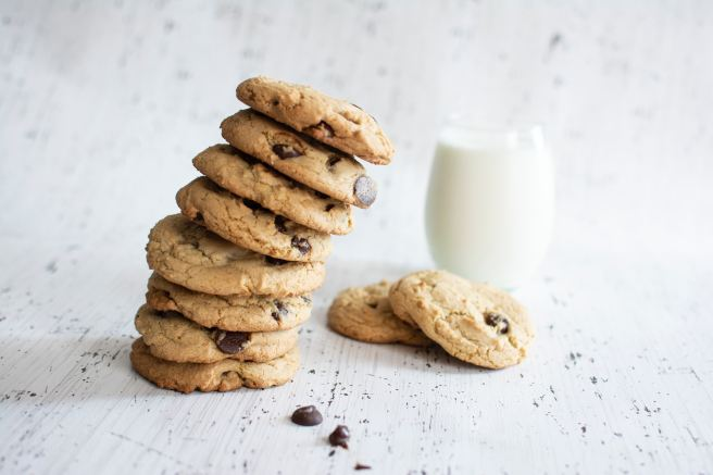 A stack of biscuits next to a glass of milk
